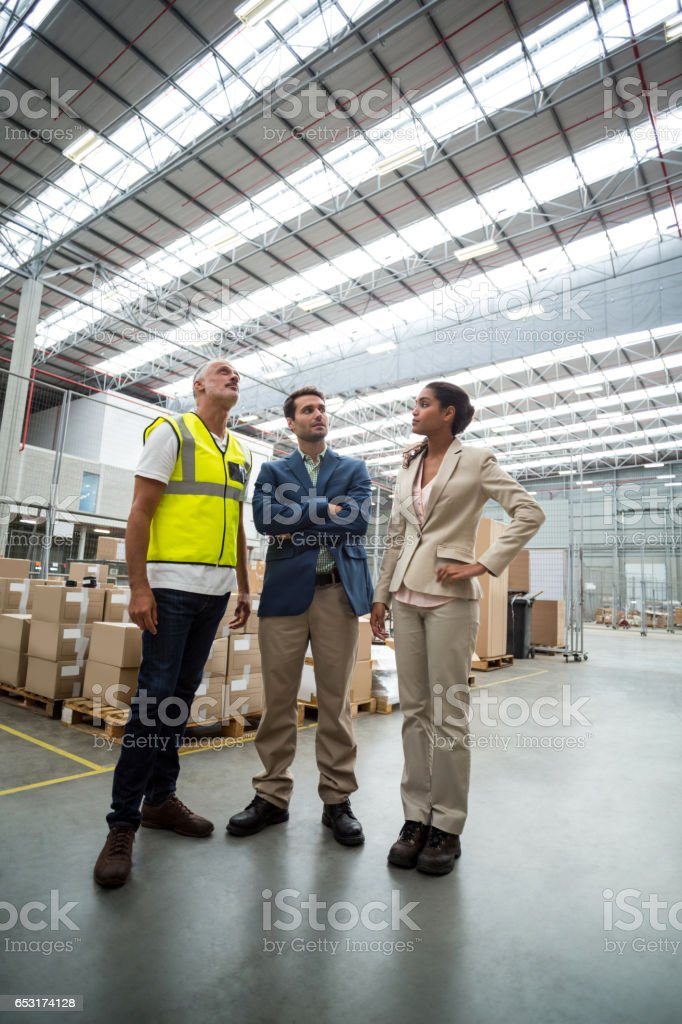 Warehouse managers discussing with the worker stock photo