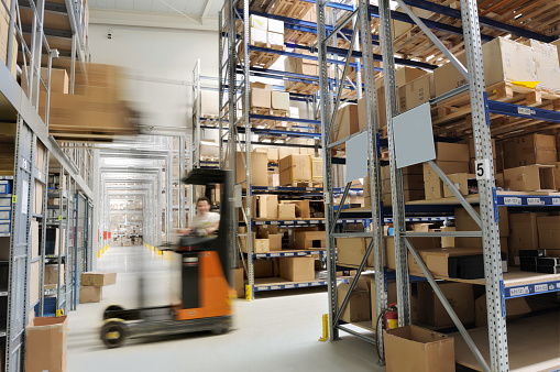 Indoor manufacturing and storage details. Warehouse aisle with shelving and a forklifter, cardboard boxes and other merchandise.