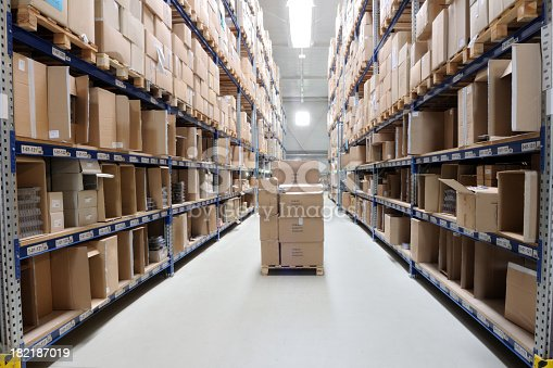 Indoor manufacturing and storage details. Warehouse aisle with shelving, cardboard boxes and other merchandise.