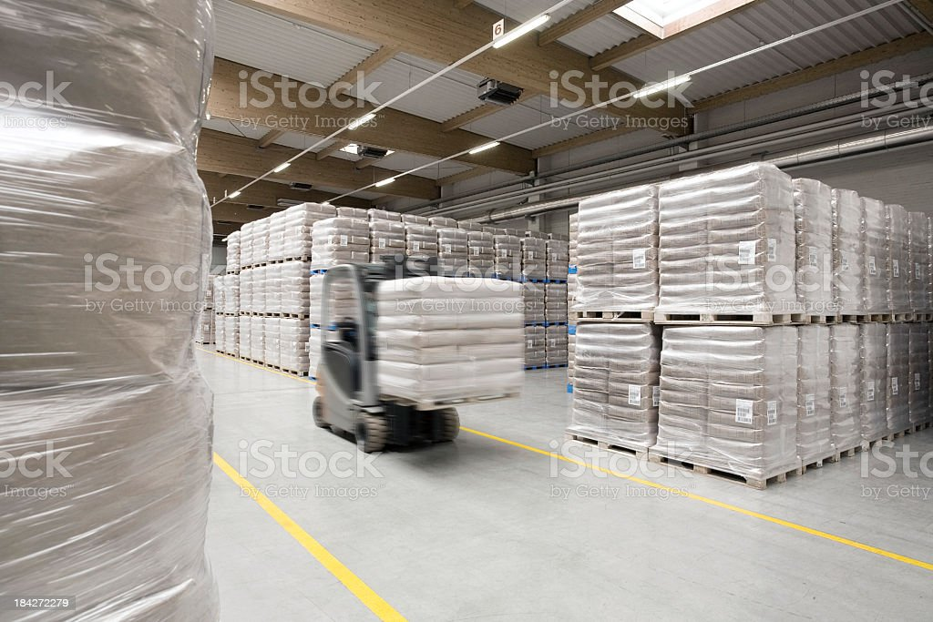 Warehouse row and fork-lift passing royalty-free stock photo