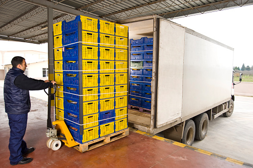 worker loading plastic crates in truck