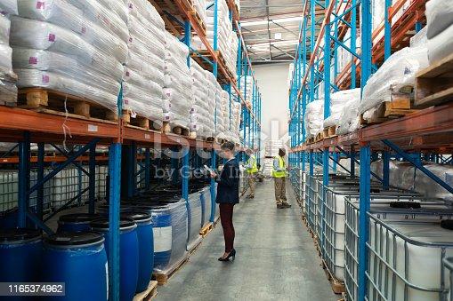 1165379503istockphoto Warehouse staff checking stocks in warehouse 1165374962