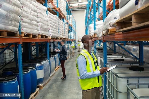 1165379503istockphoto Warehouse staff checking stocks in warehouse 1165375144