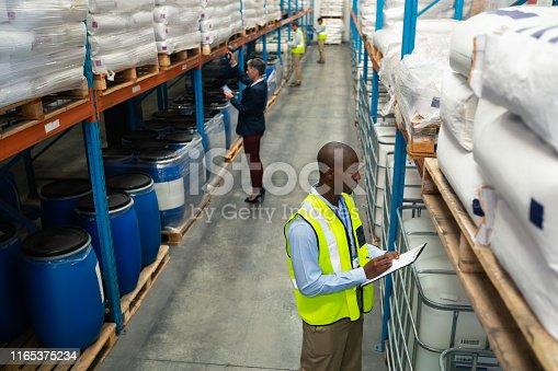 1165379503istockphoto Warehouse staff checking stocks in warehouse 1165375234