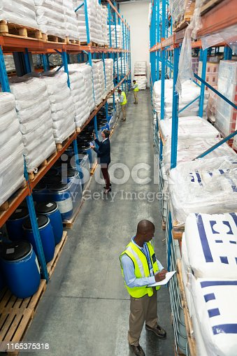 1165379503istockphoto Warehouse staff checking stocks in warehouse 1165375318