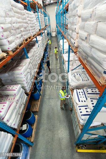 1165379503istockphoto Warehouse staff checking stocks in warehouse 1165375397