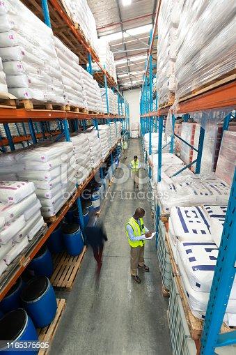 1165376915istockphoto Warehouse staff checking stocks in warehouse 1165375505
