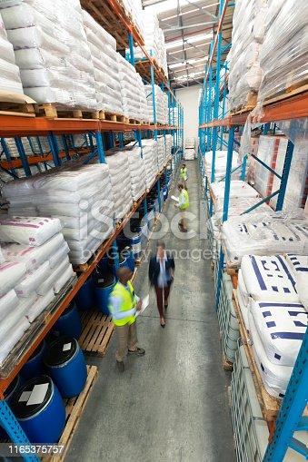1165376915istockphoto Warehouse staff checking stocks in warehouse 1165375757