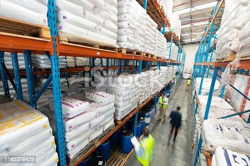 1165376915istockphoto Warehouse staff checking stocks in warehouse 1165376429