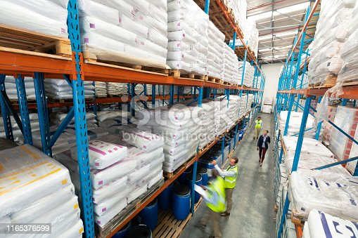 1165376915istockphoto Warehouse staff checking stocks in warehouse 1165376599