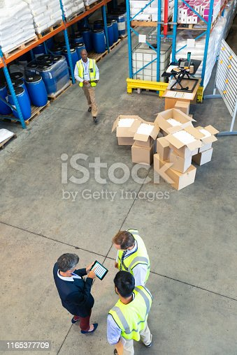 1165379503istockphoto Warehouse staff discussing over digital tablet in warehouse 1165377709