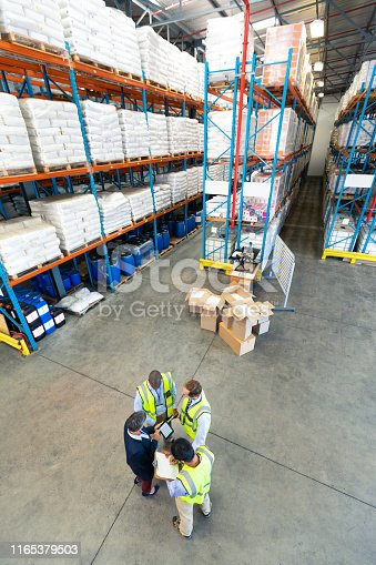 istock Warehouse staff discussing over digital tablet in warehouse 1165379503