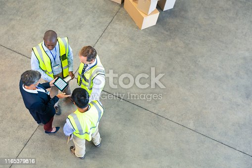1165379503istockphoto Warehouse staff discussing over digital tablet in warehouse 1165379816