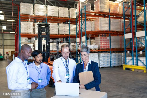 1165379503istockphoto Warehouse staff discussing over laptop in warehouse 1165369939