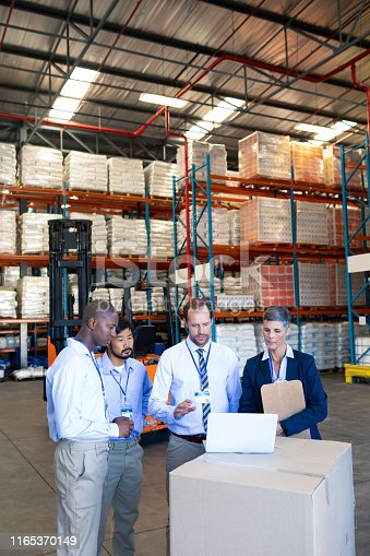 1165379503istockphoto Warehouse staff discussing over laptop in warehouse 1165370149