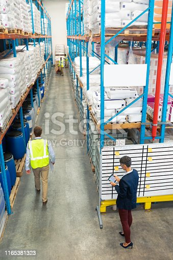 1165379503istockphoto Warehouse staff working together in warehouse 1165381323