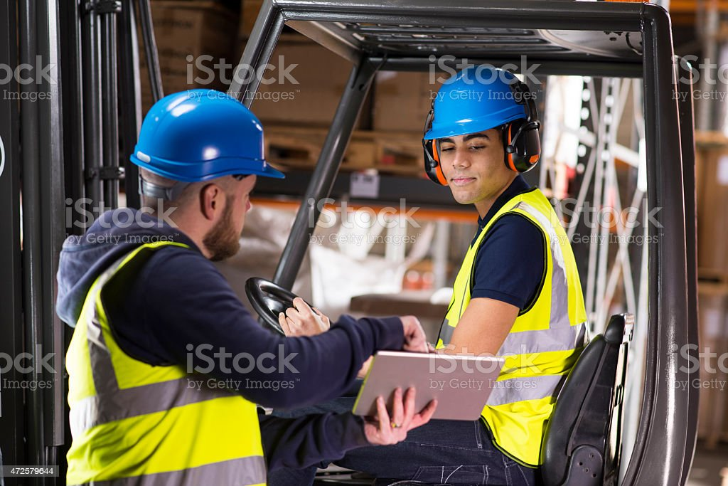 warehouse supervisor chats to young forklift truck driver trainee stock photo