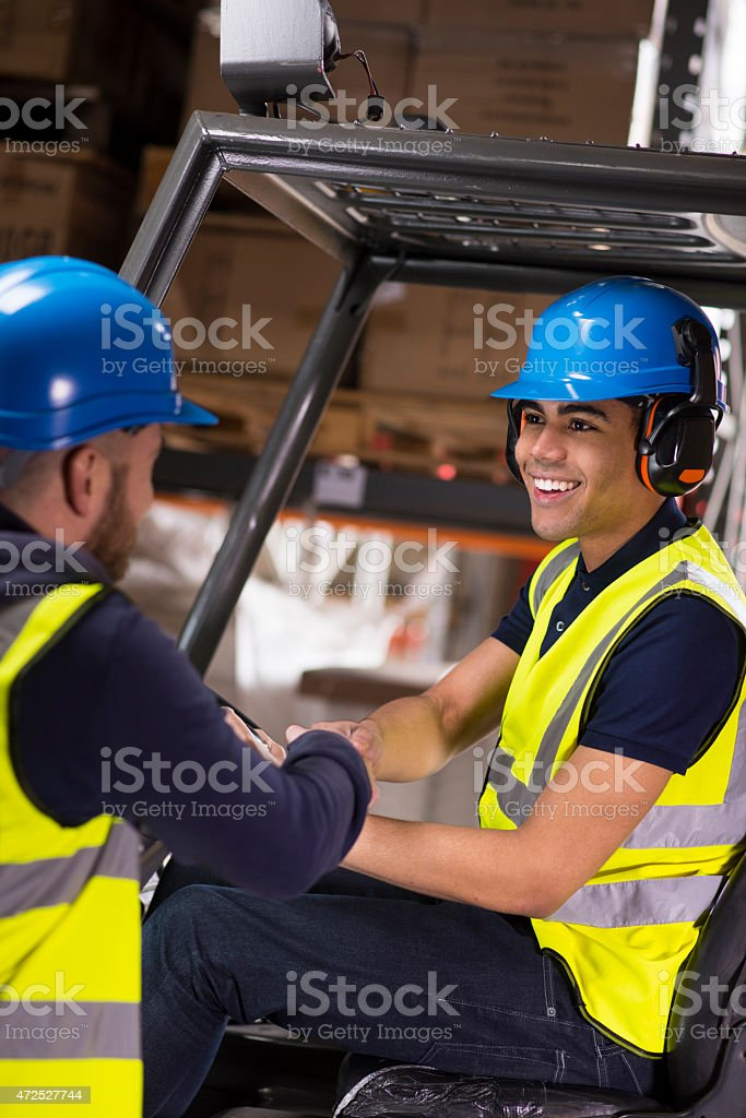 warehouse supervisor congratulates young forklift truck driver trainee stock photo