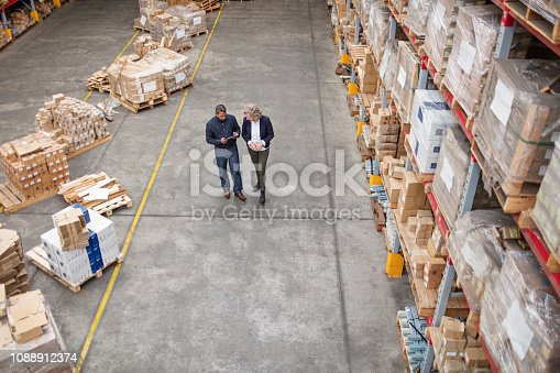 Supervisor walking and talking with senior female manager in warehouse. Warehouse employees preparing a stock list.