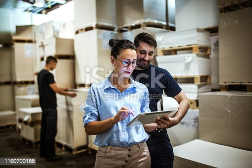 istock Warehouse supervisor walking and talking with senior manager 1160700188