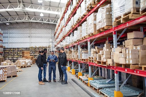 Mature manager with digital tablet discussing work with logistics team. Warehouse worker meeting over delivery schedule.