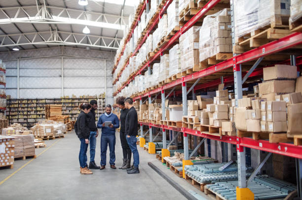 Warehouse team meeting Mature manager with digital tablet discussing work with logistics team. Warehouse worker meeting over delivery schedule. warehouse stock pictures, royalty-free photos & images