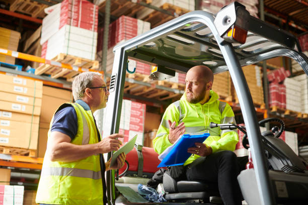 warehouse teamwork fork lift truck driver in warehouse chats to supervisor driving instructor stock pictures, royalty-free photos & images