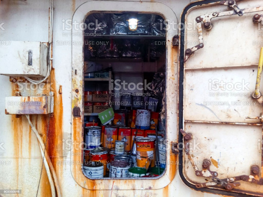 Warehouse with paint and household tools. The porthole of the porthole in the ship's cabin stock photo