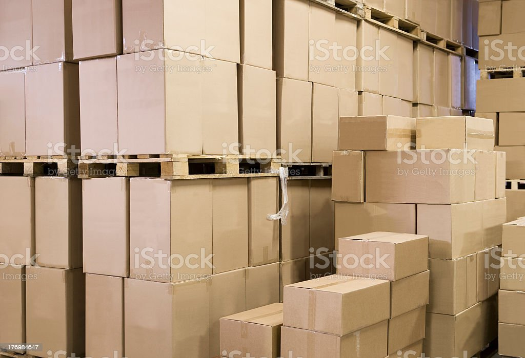 Warehouse with stack of blank cardboard boxes stock photo