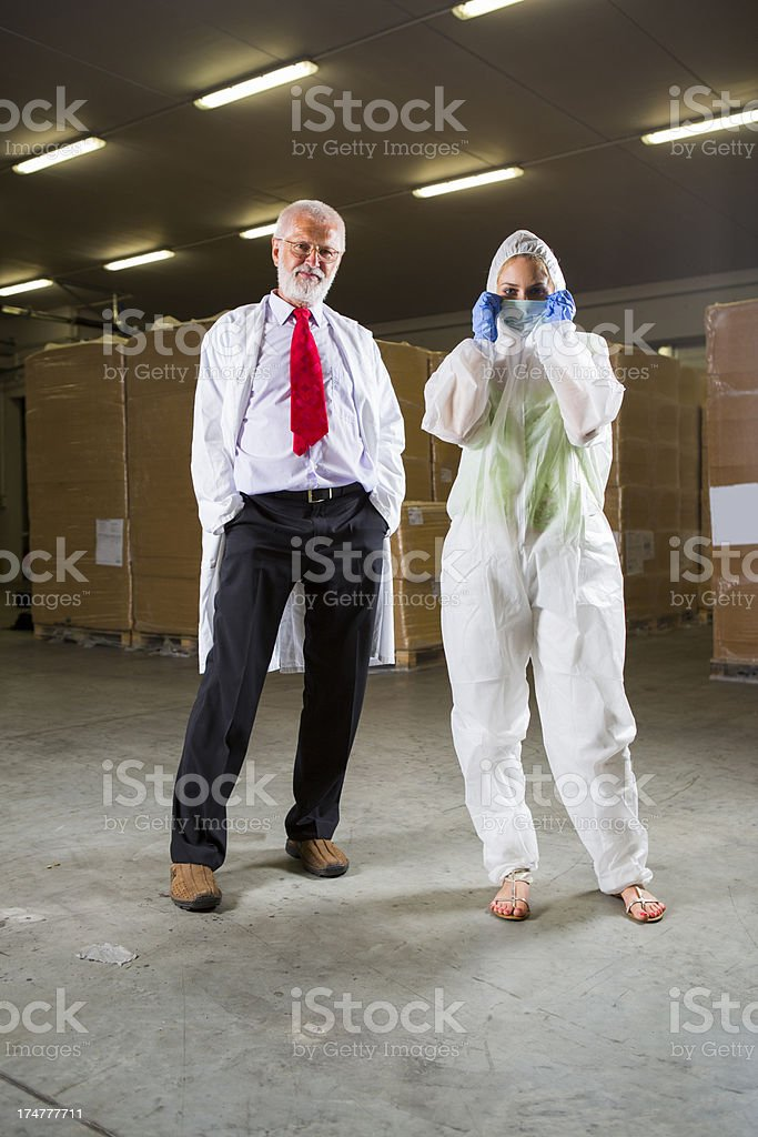 Warehouse worker and beautiful supervisor in a hazmat suit royalty-free stock photo