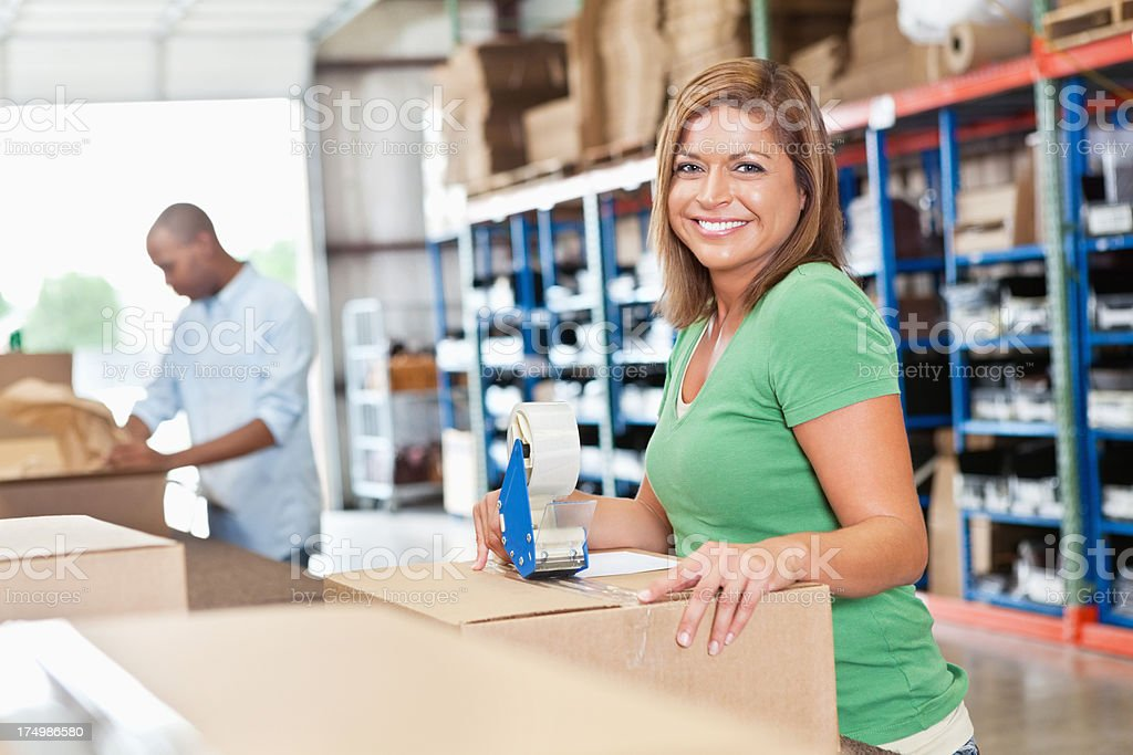 Warehouse worker assembling boxes in shipping distribution assembly line royalty-free stock photo