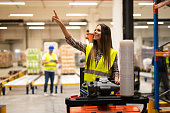 Forklift operator looking for an empty space on a shelf in warehouse distribution center.