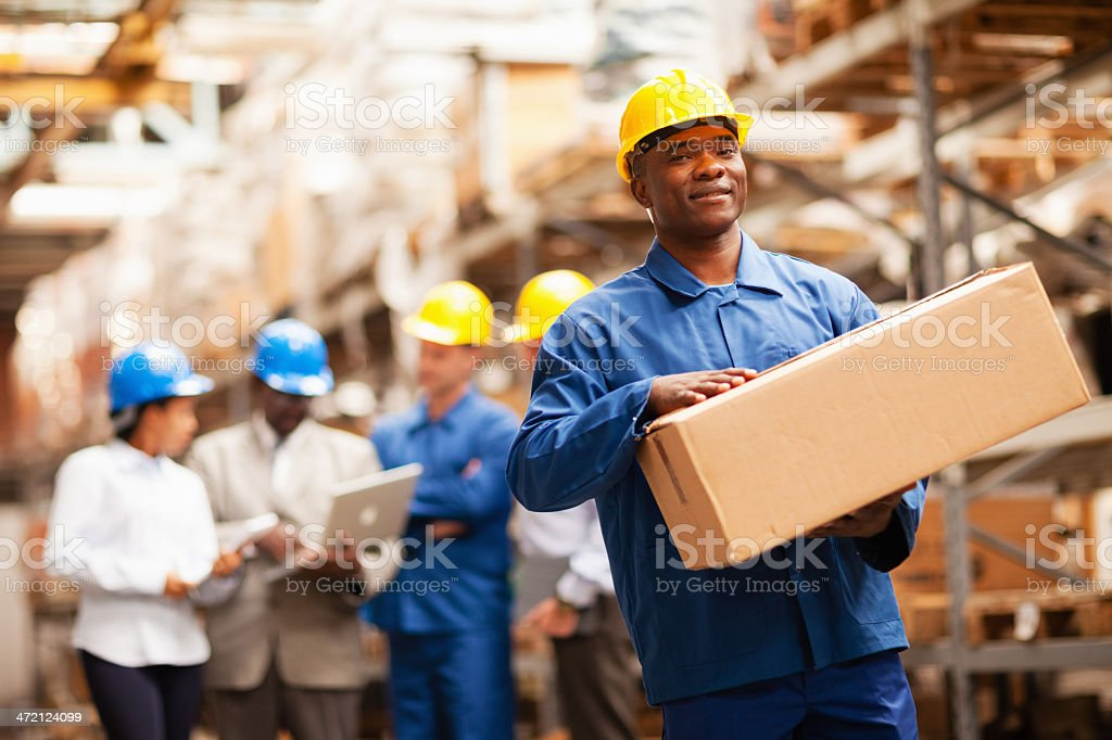 Warehouse worker carrying box stock photo