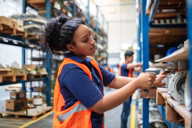 Warehouse worker checking cargo on shelves with scanner stock photo