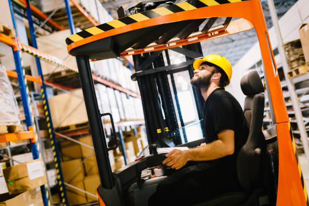 Warehouse worker doing logistics work with forklift loader Warehouse industry worker doing logistics work with forklift loader driver occupation stock pictures, royalty-free photos & images