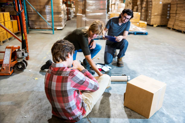 A warehouse worker fallen after tripping on some debris.  He is clutching his ankle in pain as two supervisors assists him. stock photo