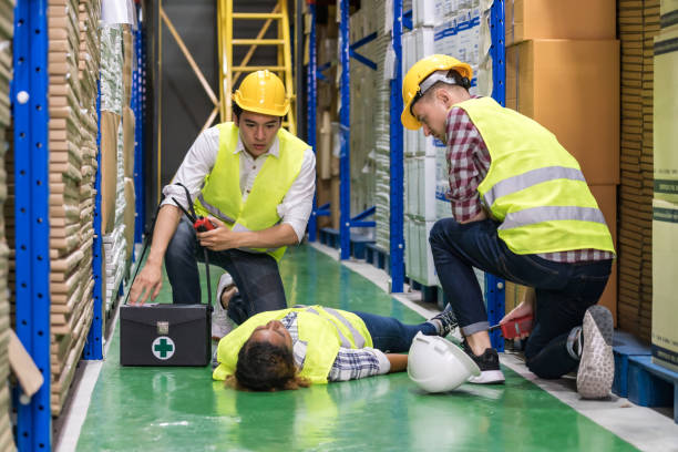 Warehouse worker frist aid after accident. stock photo