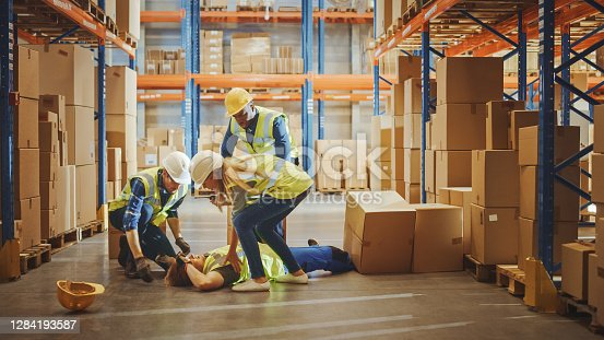 istock Warehouse Worker Has Work Related Accident Falls while Trying to Pick Up Cardboard Box from the Shelf. Colleagues Call for Help and Medical Assistance. Injury at Work. 1284193587