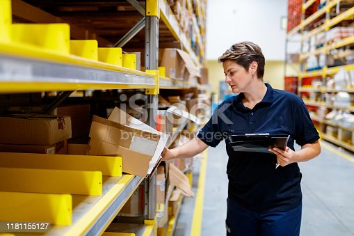 Female warehouse worker holding checklist and checking content of box in warehouse