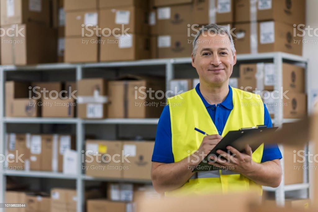 Trabajador de almacén con portapapeles en un gran almacén - foto de stock