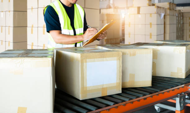 Warehouse worker holding clipboard writing on paper for shipment goods Warehouse worker holding clipboard writing on paper for shipment goods, package boxes sorting on conveyor belt, distribution warehouse inventory management, delivery transport, logistics distribution center stock pictures, royalty-free photos & images