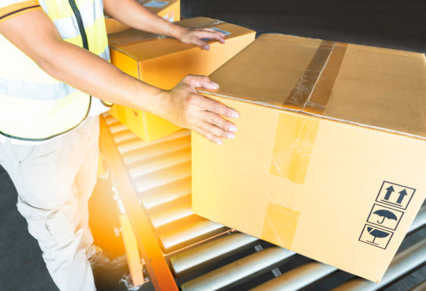 Warehouse worker is sorting cardboard boxes on rollers conveyor at distribution warehouse Warehouse worker in uniform is sorting cardboard boxes on rollers conveyor distribution center stock pictures, royalty-free photos & images