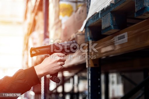 Warehouse worker is using a barcode scanner