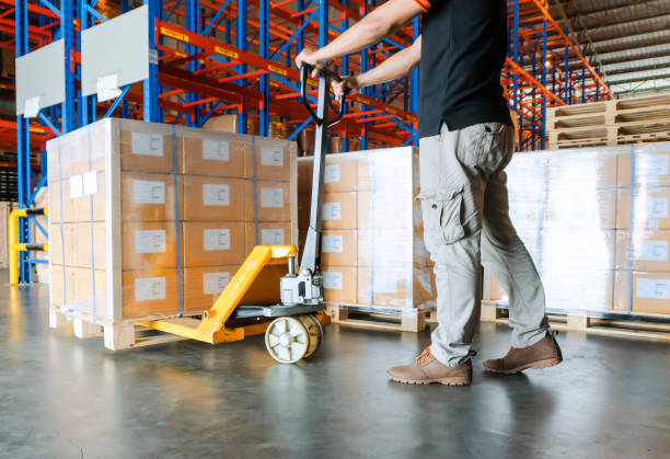 Warehouse worker is working with hand pallet truck and cargo pallet Warehouse courier cargo shipment, inventory management pallet jack stock pictures, royalty-free photos & images