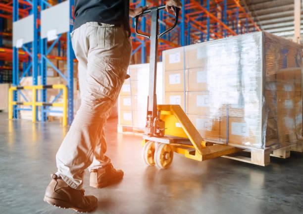 창고 노동자가 핸드 팔레트 트럭 및 화물 팔레트로 작업하고 있습니다. - 저장고 제작물 뉴스 사진 이미지