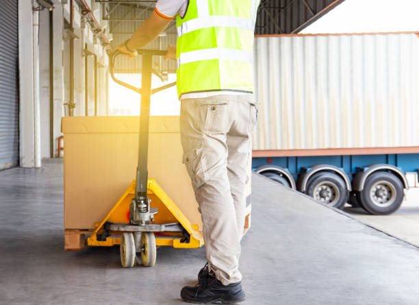 Warehouse worker is working with hand pallet truck and shipment pallet Warehouse cargo courier shipment unloading into a trucks pallet jack stock pictures, royalty-free photos & images