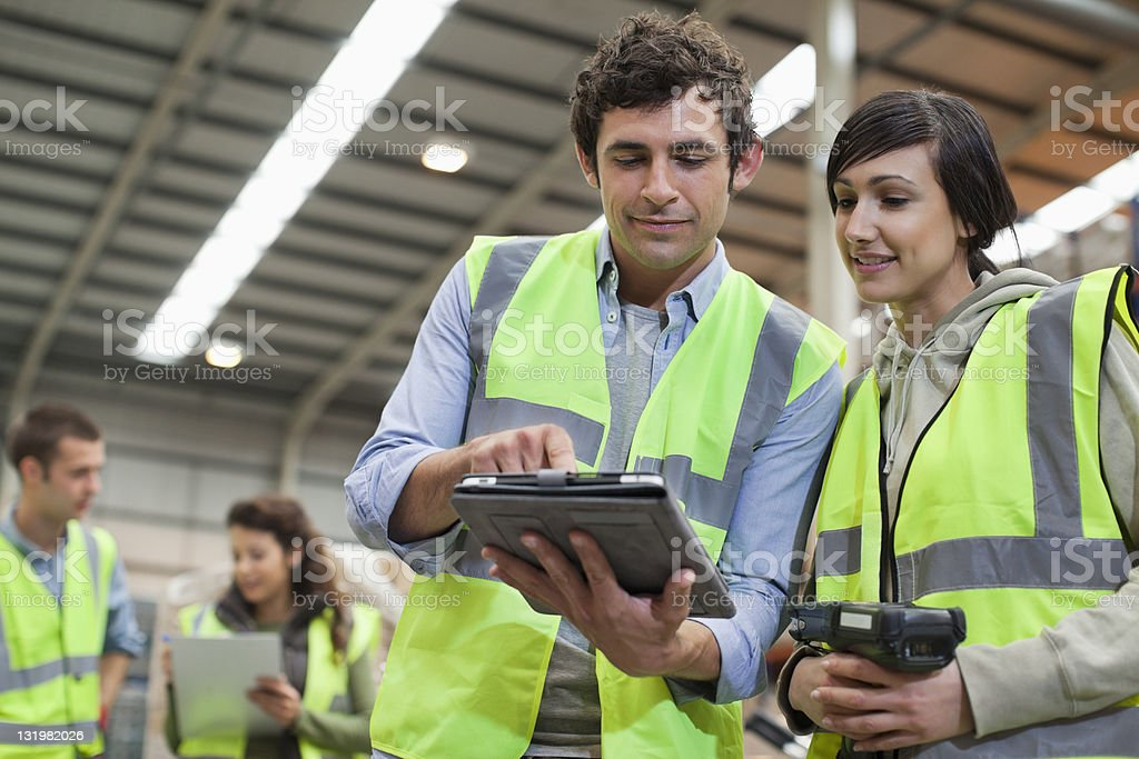 Warehouse worker looking at digital tablet royalty-free stock photo