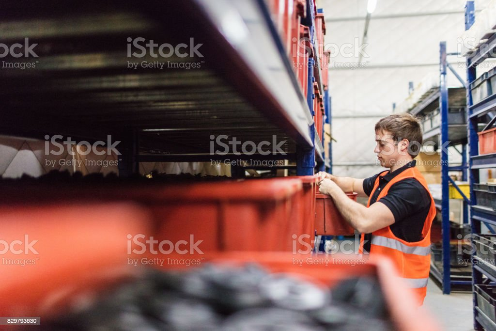 Warehouse worker looking for material on shelves stock photo
