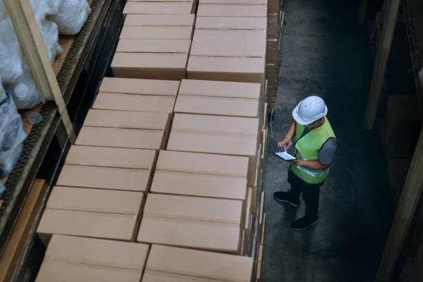 Warehouse worker man with safety hard hat is checking order details with a digital tablet at inventory room stock photo