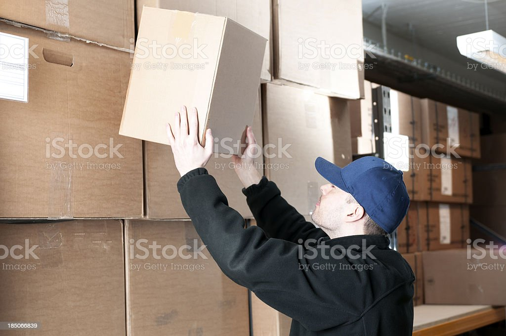 Warehouse worker moves a cardboard box royalty-free stock photo